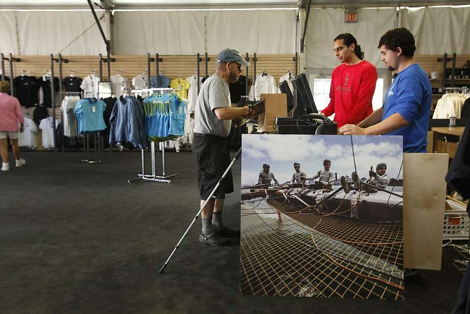 Web Otis (left) of San Francisco makes a purchase at the America's Cup Team Store on Pier 27. Photo: Lea Suzuki, The Chronicle