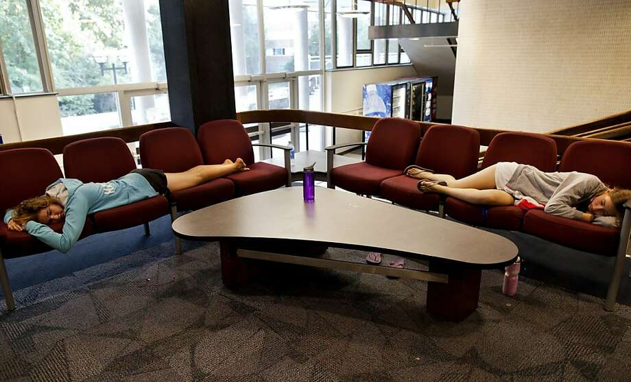 Undergraduates Noelle Hansford (left) and Andrea Case nap in the lobby of Bursley Hall, a dormitory at the University of Michigan in Ann Arbor. Photo: Joseph Xu, Associated Press