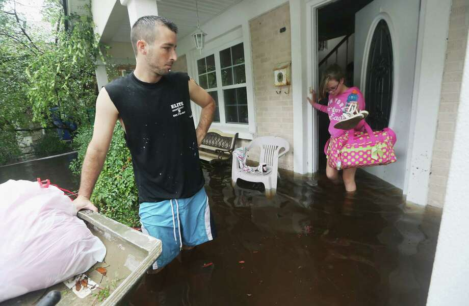 Brittany Trumbaturi departs her flooded home in Slidell, La., on Thursday with family member Joshua Barbot, who came in a boat to rescue relatives. Photo: Mario Tama / 2012 Getty Images
