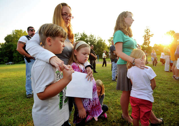 "Holly Carlson, left, holds her children, Kodie, left, and Kaitlynn, as Karen McBride holds her daughter, Jocelyn, after joining the crowd in the singing of ""Amazing Grace"" during the Thursday, Aug. 30, 2012 vigil at John Pettibone School in New Milford for the victims in the home explosion that occured Wednesday, killing one and severely injuring two. Photo: Jason Rearick / The News-Times"