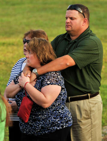 New Milford resident Chris Rigdon holds his wife, Lynette, during the Thursday, Aug. 30, 2012 vigil at John Pettibone School in New Milford for the victims in the home explosion that occured Wednesday, killing one and severely injuring two. Photo: Jason Rearick / The News-Times