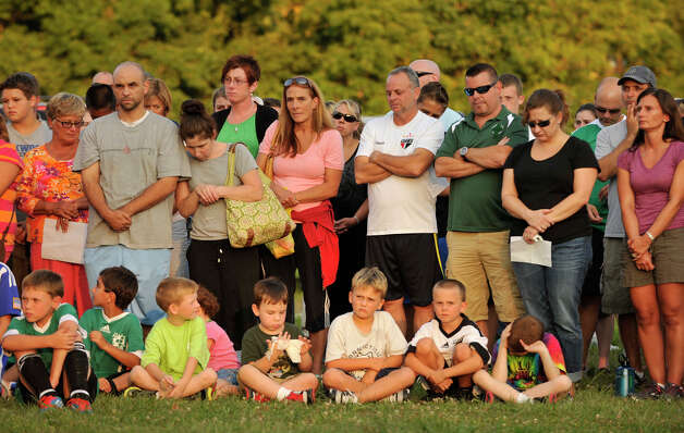 People stand during the Thursday, Aug. 30, 2012 vigil at John Pettibone School in New Milford for the victims in the home explosion that occured Wednesday, killing one and severely injuring two. Photo: Jason Rearick / The News-Times