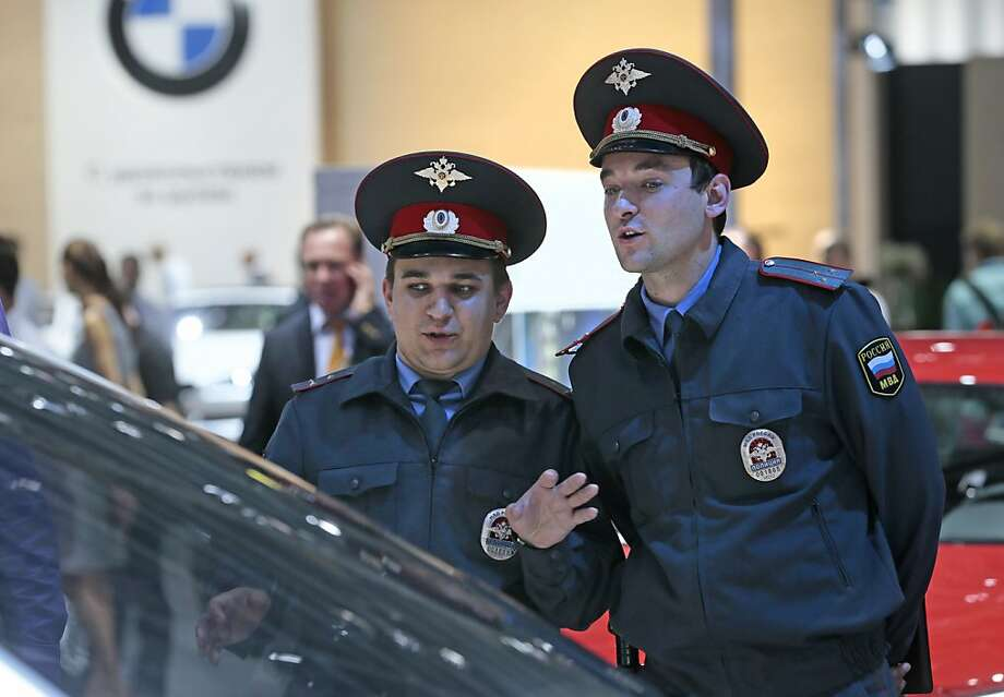 Two Russian police officers look at a BMW car at the Moscow International Automobile Salon in Moscow, Thursday, Aug. 30, 2012.  Photo: Mikhail Metzel, Associated Press