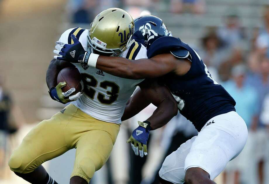 HOUSTON, TX - AUGUST 30:  Johnathan Franklin #23 of the UCLA Bruins is tackled by Corey Frazier #20 of the Rice Owls during their game at Rice Stadium on August 30, 2012 in Houston, Texas. Photo: Scott Halleran, Getty Images / 2012 Getty Images