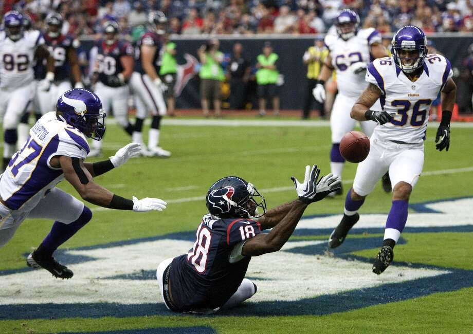 Wide receiver Lestar Jean drops a pass as he's pressured by Vikings safety Eric Frampton, and cornerback Robert Blanton during the second quarter. (Cody Duty / © 2011 Houston Chronicle)