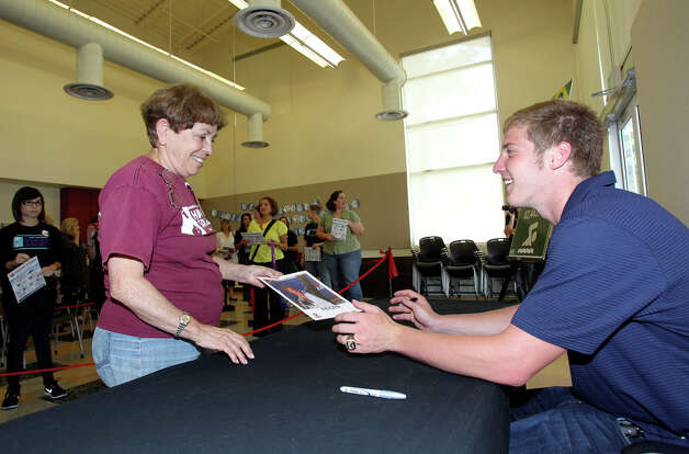 Jimmy Feigen gives an autographed picture to Joan Pfeifer as he meets with fans at the San Antonio Humane Society on August 30, 2012. Photo: Tom Reel, Express-News / ©2012 San Antono Express-News