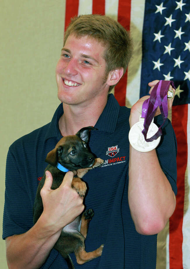 Jimmy Feigen holds a puppy, Cargill, and his silver medal as he  meets with fans at the San Antonio Humane Society on August 30, 2012. Photo: Tom Reel, Express-News / ©2012 San Antono Express-News