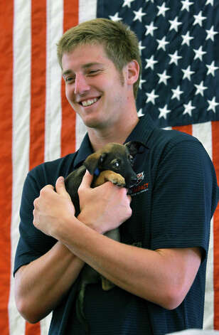 Jimmy Feigen holds Cargill, an 8 week old puppy, as he meets with fans at the San Antonio Humane Society on August 30, 2012. Photo: Tom Reel, Express-News / ©2012 San Antono Express-News