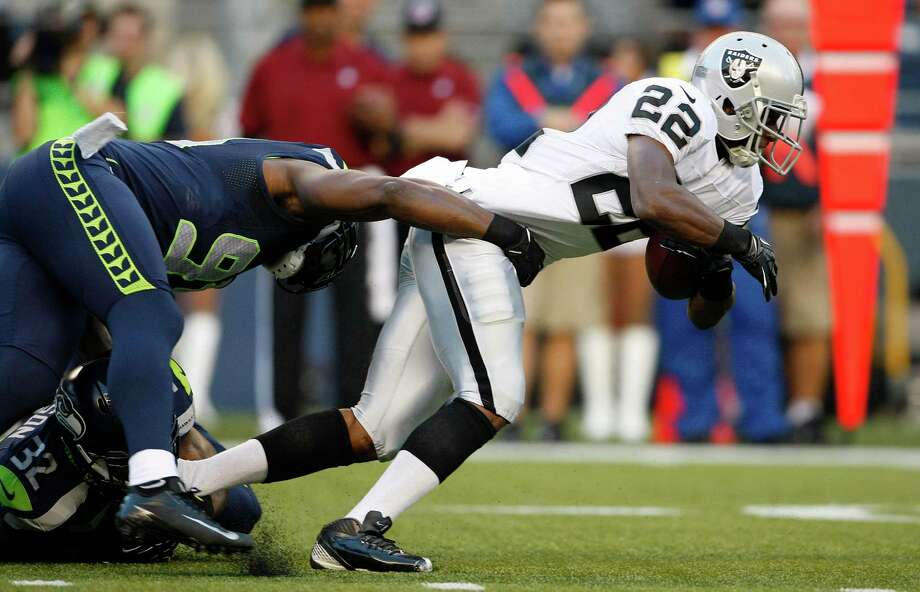 Seattle Seahawks' Chris Clemons, left, grabs Oakland Raiders' Taiwan Jones on a rush in the first half. Photo: AP
