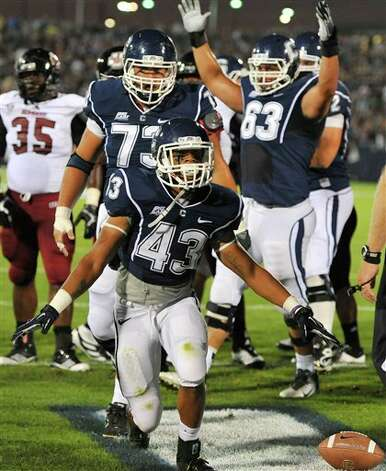 UConn's Lyle McCombs (43) celebrates his touchdown against Massachusetts in the  first half of an NCAA college football game in East Hartford, Conn.,  Thursday, Aug. 30, 2012. (AP Photo/Jessica Hill)