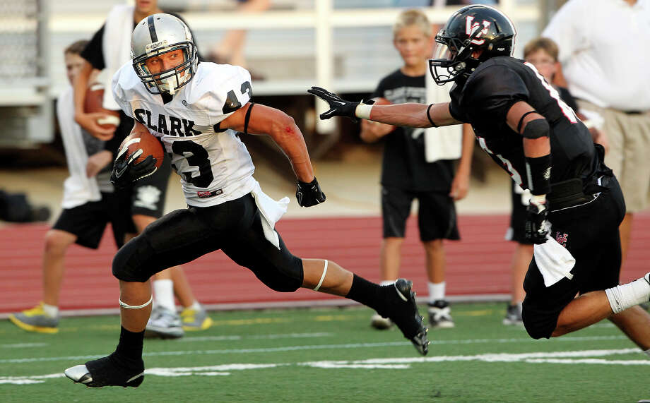 Clark's Branden Valle looks back at the prusuing Jacob Livingston as he breaks to the open on the right for a touchdown as Churchill hosts Clark in the Gucci Bowl at Comalander Stadiumon August 30, 2012. Photo: Tom Reel, Express-News / ©2012 San Antono Express-News