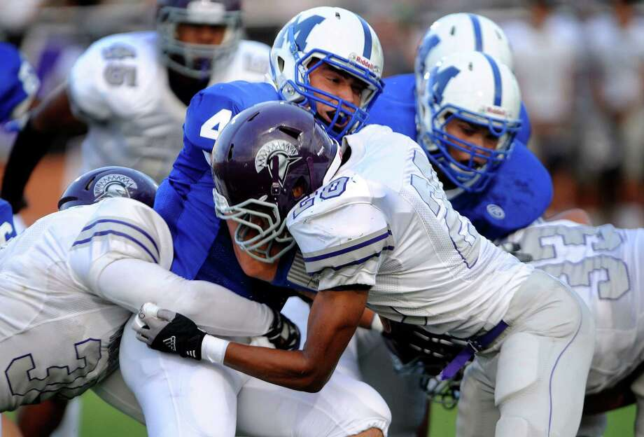 MacArthur quarterback Carson Keller (4) is tackled by Jauchai Pullen (20) of Warren during high-school football action at Heroes Stadium on Thursday, Aug. 30, 2012. Photo: Billy Calzada, Express-News / © San Antonio Express-News