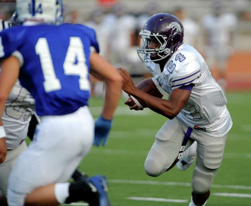 Ronald Jacobs of Warren High runs for yardage against MacArthur during high-school football action at Heroes Stadium on Thursday, Aug. 30, 2012.