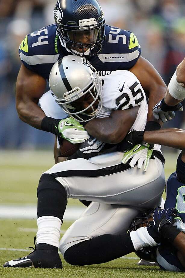 Raiders running back Mike Goodson gets wrapped up by the Seahawks' Bobby Wagner in first-half action. Photo: Kevin P. Casey, Associated Press