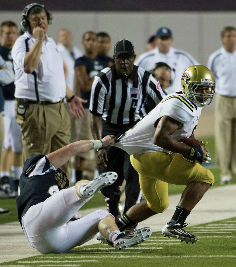 UCLA running back Jordon James (6) breaks away from Rice linebacker Kyle Prater (44) during the second half. Photo: Smiley N. Pool, Houston Chronicle / © 2012  Houston Chronicle