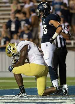 UCLA running back Johnathan Franklin kneels in prayer after scoring on a 22-yard touchdown run during the second half as Rice cornerback Phillip Gaines looks on. Photo: Smiley N. Pool, Houston Chronicle / © 2012  Houston Chronicle
