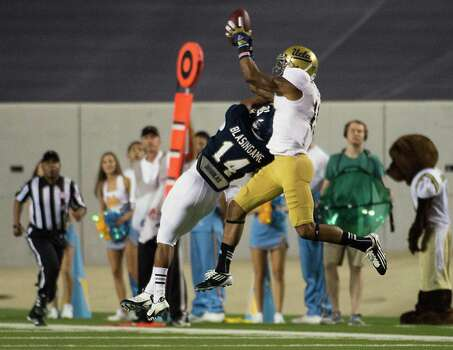 UCLA wide receiver Devin Lucien (15) Rice cornerback J.T. Blasingame (14). Photo: Smiley N. Pool, Houston Chronicle / © 2012  Houston Chronicle