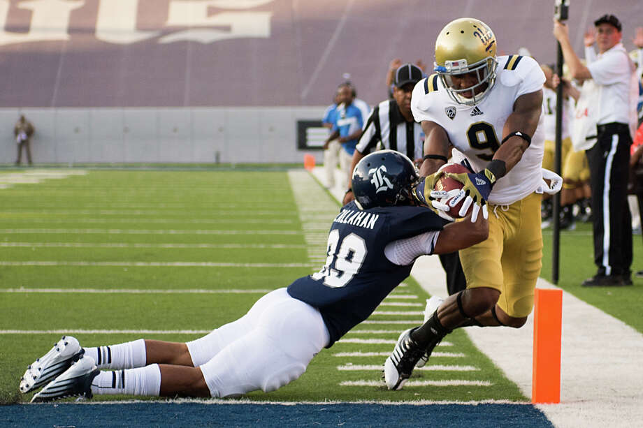 UCLA wide receiver Jerry Johnson (9) scores on a 11-yard touchdown reception past Rice Owls cornerback Bryce Callahan (29) during the first quarter. Photo: Smiley N. Pool, Houston Chronicle / © 2012  Houston Chronicle