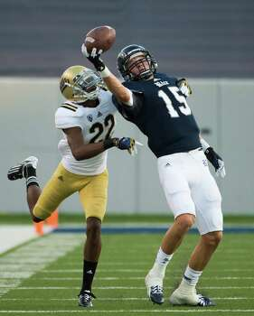 Rice Owls wide receiver Jordan Taylor (15) makes a one-handed catch as UCLA Bruins cornerback Sheldon Price (22) defends during the first quarter. Photo: Smiley N. Pool, Houston Chronicle / © 2012  Houston Chronicle