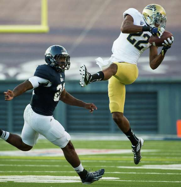 UCLA cornerback Sheldon Price (22) intercepts a pass intended for Rice Owls running back Charles Ros