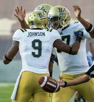 UCLA Bruins wide receiver Jerry Johnson (9) celebrates with quarterback Brett Hundley (17) after scoring on a 11-yard touchdown reception during the first quarter. Photo: Smiley N. Pool, Houston Chronicle / © 2012  Houston Chronicle