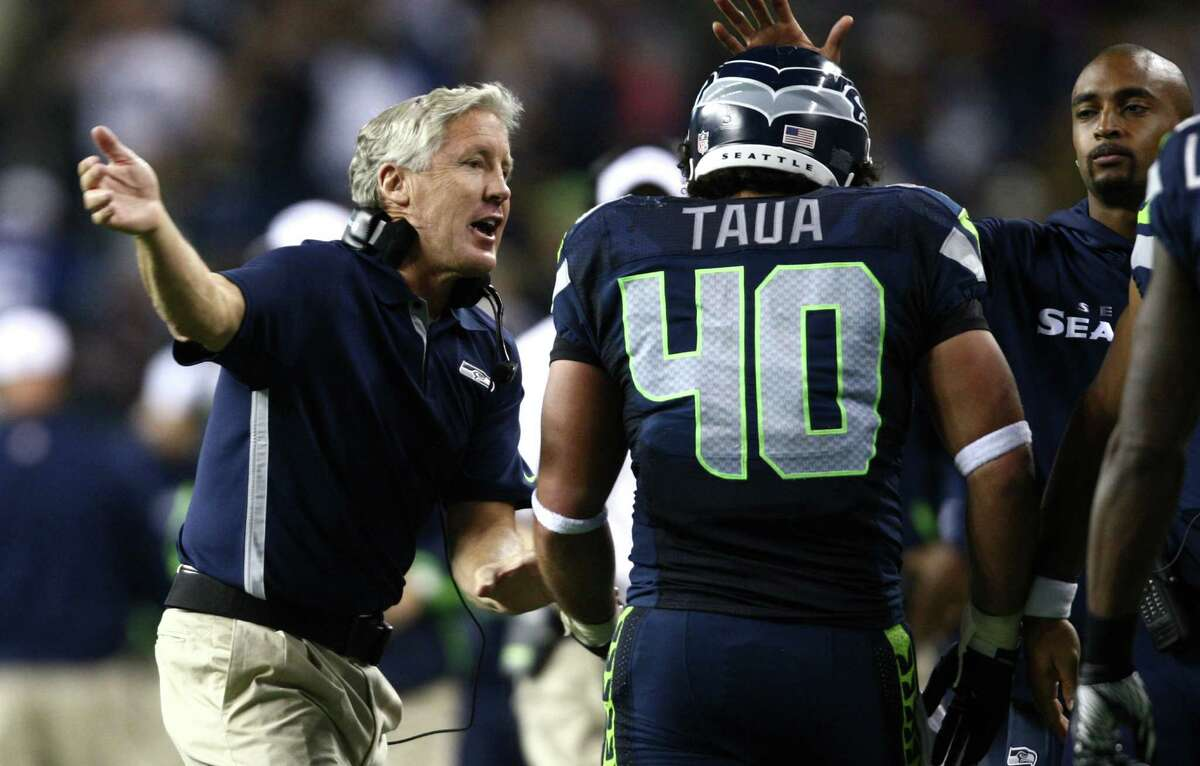 Seattle Seahawks coach Pete Carroll congratulates Vai Taua after a two yard run for a touchdown in the second quarter against the Oakland Raiders during a preseason game at CenturyLink Field in Seattle on Thursday, Aug. 30, 2012.