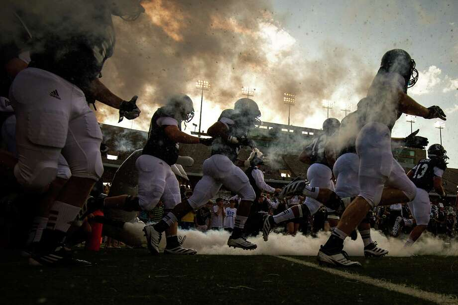 Rice Owls players race onto the field to take on UCLA in their season opener against UCLA. Photo: Smiley N. Pool, Houston Chronicle / © 2012  Houston Chronicle