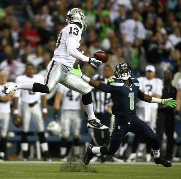 Seattle Seahawk Jeremy Lane takes control of a pass intended for Oakland Raider Brandon Carswell dur