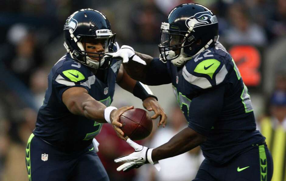 Seattle Seahawks quarterback Russell Wilson hands off the ball to Robert Turbin (22).