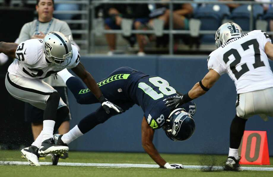 Seattle Seahawks player Golden Tate nears the out of bounds line as he pulls down a pass against Oakland Raiders player Shawntae Spencer and Matt Giordano (27) in a play challenged. Photo: JOSHUA TRUJILLO / SEATTLEPI.COM