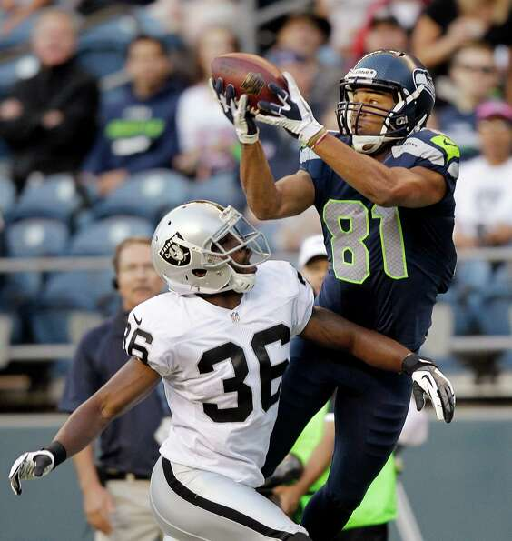 Seattle Seahawks' Golden Tate (81) catches the ball in front of Oakland Raiders' Shawntae Spencer in