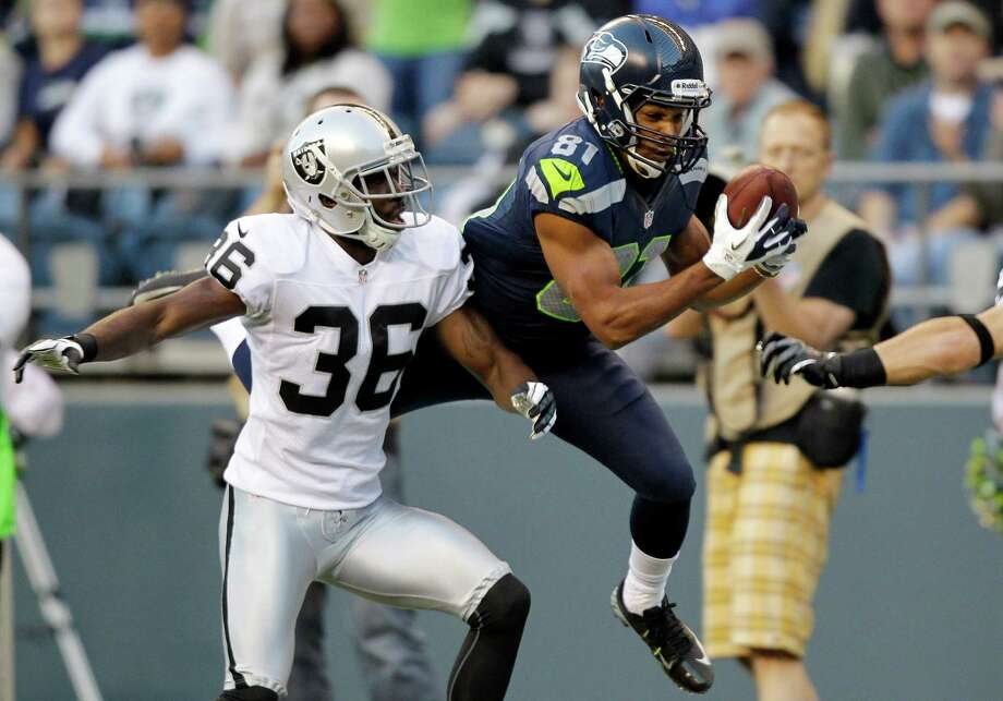 Seattle Seahawks' Golden Tate, right, catches the ball in front of Oakland Raiders' Shawntae Spencer in the first half. Photo: AP