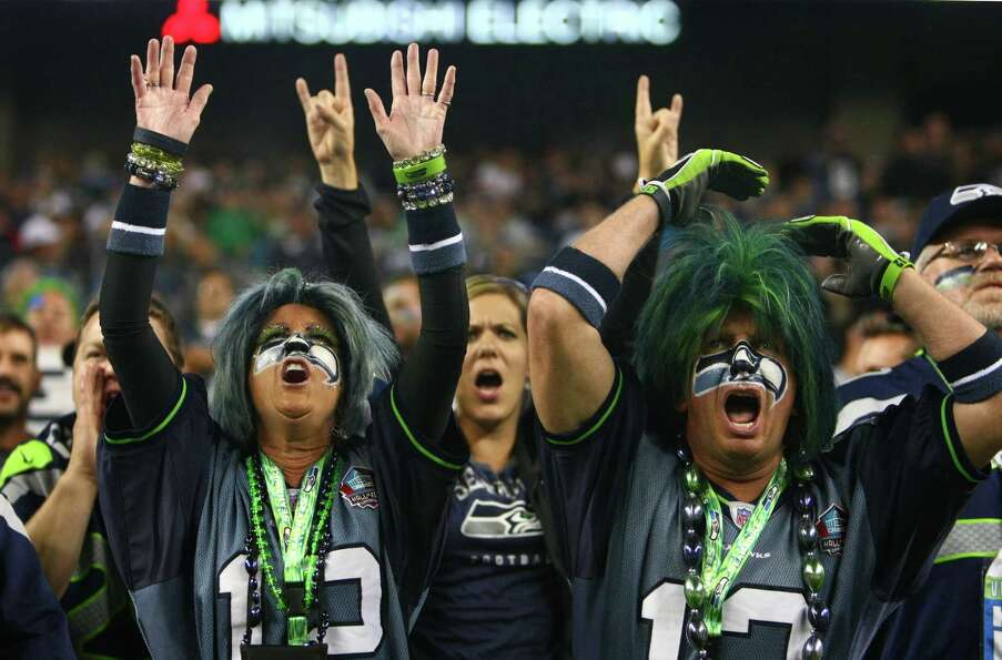 Seattle Seahawks fans Jeff and Dede Schumaier cheer for their team against the Oakland Raiders durin