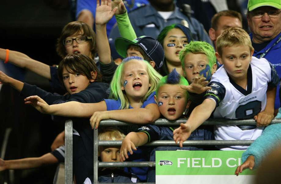 Young fans try to get the attention of Seattle Seahawks players and cheerleaders during a preseason game against the Oakland Raiders on Thursday, August 30, 2012 at CenturyLink Field in Seattle. The Hawks defeated the Raiders 21 to 3. Photo: JOSHUA TRUJILLO / SEATTLEPI.COM