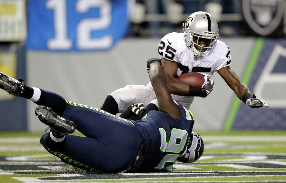 Seattle Seahawks' Jaye Howard (94) brings down Oakland Raiders' Mike Goodson in the endzone for a safety in the second half of a preseason NFL football game Thursday, Aug. 30, 2012 in Seattle. Photo: AP