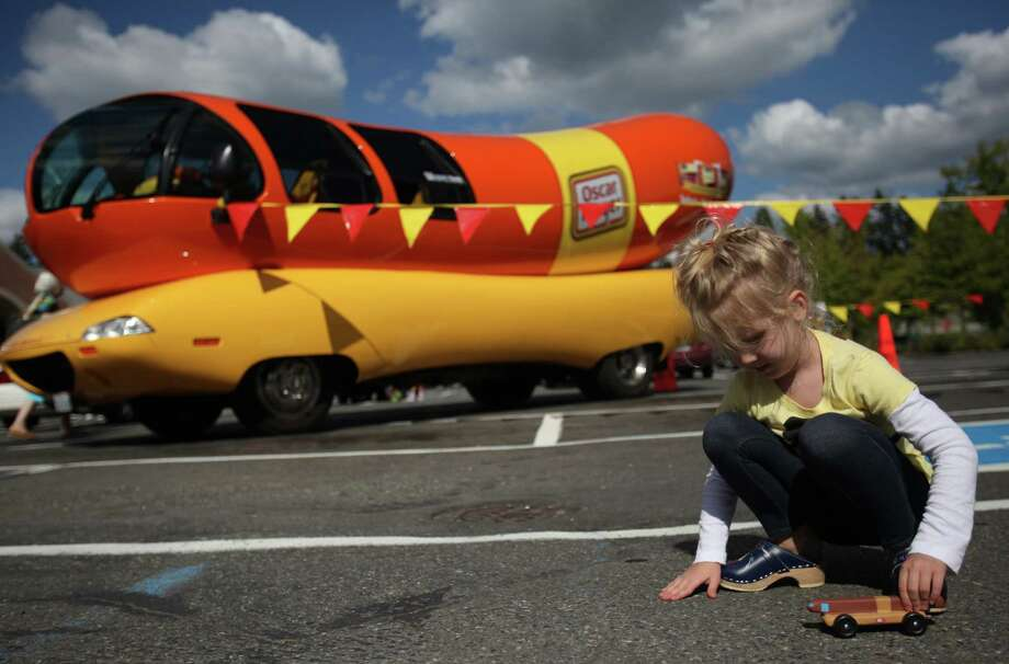 Sigrid Strombo, 5, plays with the Oscar Mayer Wienermobile Pinewood Derby car made by her dad Gary during his time in Kabul, Afghanistan. The car became a favorite toy of hers while her dad was working with the Army in Afghanistan. Her dad has been back for two months and took his daughter to see the real Oscar Mayer Wienermobile during a stop in front of Albertson's in Lake Forest Park on Thursday, August 30, 2012. The unique vehicle is touring the Seattle area. Photo: JOSHUA TRUJILLO / SEATTLEPI.COM