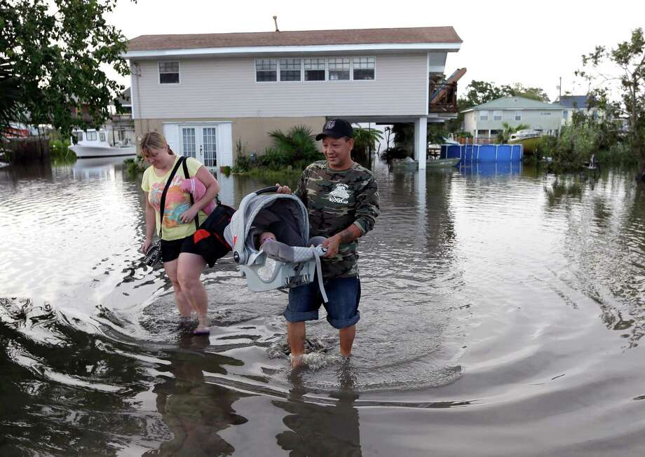 Tony Rodriguez, right, carries his baby daughter Nicole as they and his wife Jodi Clelland leave their flooded home in the aftermath of Hurricane Isaac in Slidell, La., Friday, Aug. 31, 2012. Isaac is now a tropical depression and the center was on track to cross Arkansas on Friday and southern Missouri on Friday night, spreading rain as it goes. (AP Photo/David J. Phillip) Photo: David J. Phillip, Associated Press / AP