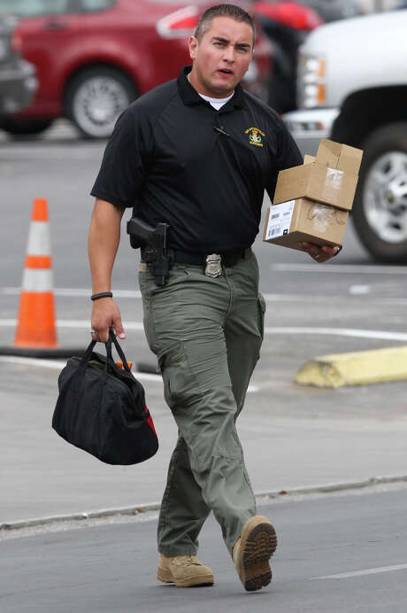A member of the San Antonio Police Department's bomb squad carries two packages described as suspicious away from a building on the 800 block of Dolorosa Friday August 31, 2012. The boxes were found under a mail box and a United Parcel Service box behind the Washington Square building which houses a number of Federal, city and private offices. According to Sgt. Javier Salazar of the San Antonio Police Department, the boxes were locally addressed and contained electronics. Photo: John Davenport, San Antonio Express-News / San Antonio Express-News