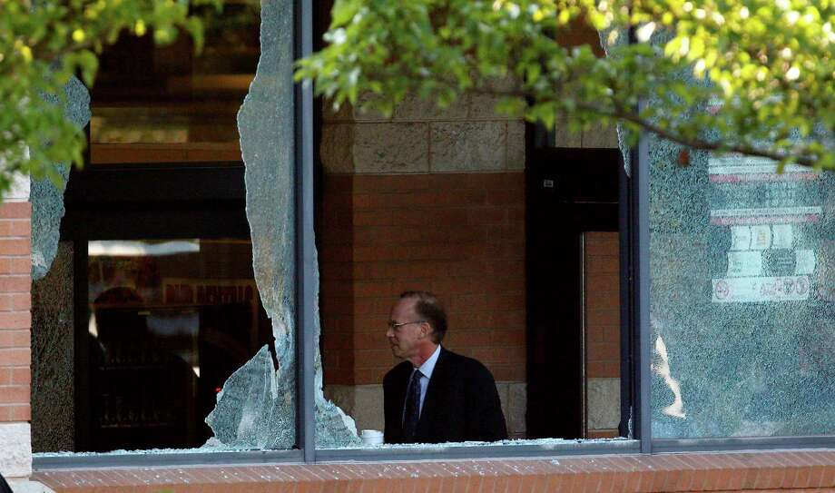 Middlesex County prosecutor Bruce Kaplan is seen through two broken windows as he arrives at the scene of a shooting at a Pathmark grocery store in Old Bridge, N.J., Friday, Aug. 31, 2012. At least three people have died in the shooting. A law enforcement official briefed on the shooting says the person believed to be the shooter is among the dead.  (AP Photo/Julio Cortez) Photo: Julio Cortez