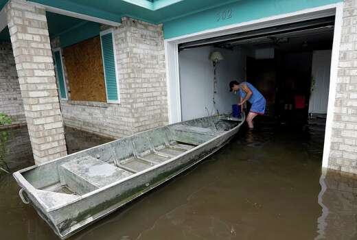 Anthony Tabb ties off a boat in his uncles flooded home as they work to recover personal items, Friday, Aug. 31, 2012, in LaPlace, La. Isaac crawled into the central U.S. on Friday, leaving behind a soggy mess in Louisiana.  It will be a few days before the water recedes and people in flooded areas can return home. New Orleans itself was spared, thanks in large part to a levee system fortified after Katrina devastated the Gulf Coast in 2005.  (AP Photo/Eric Gay) Photo: Eric Gay, Associated Press / AP