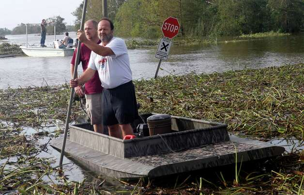 Neighbors Josh Brockhaus, left, and Cisco Gonzales, bring their boat ashore after checking their homes in after Hurricane Isaac came through the region, in Braithwaite, La.,  Friday, Aug. 31, 2012.  Isaac crawled into the central U.S. on Friday, leaving behind a soggy mess in Louisiana.  It will be a few days before the water recedes and people in flooded areas can return home. New Orleans itself was spared, thanks in large part to a levee system fortified after Katrina devastated the Gulf Coast in 2005.(AP Photo/Gerald Herbert) Photo: Gerald Herbert, Associated Press / AP
