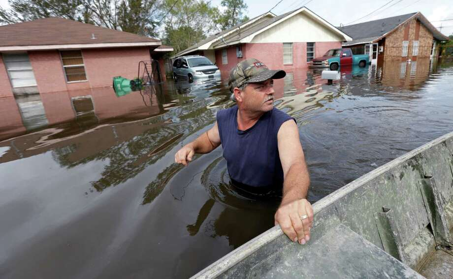 Christopher Tabb walks a boat into a flooded community to help recover items from his flooded home, Friday, Aug. 31, 2012, in LaPlace, La. Isaac crawled into the central U.S. on Friday, leaving behind a soggy mess in Louisiana.  It will be a few days before the water recedes and people in flooded areas can return home. New Orleans itself was spared, thanks in large part to a levee system fortified after Katrina devastated the Gulf Coast in 2005. (AP Photo/Eric Gay) Photo: Eric Gay, Associated Press / AP