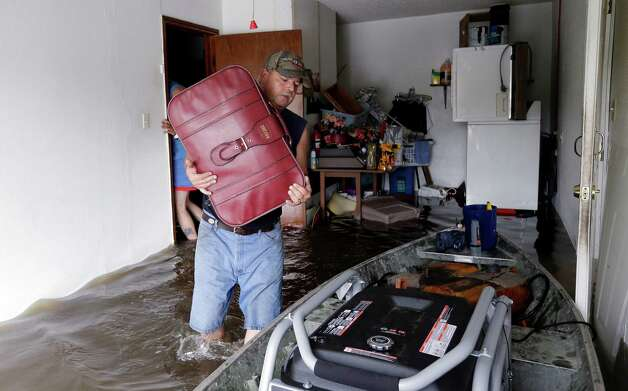 Christopher Tabb uses a boat to recover items from his home, Friday, Aug. 31, 2012, in LaPlace, La. Isaac crawled into the central U.S. on Friday, leaving behind a soggy mess in Louisiana.  It will be a few days before the water recedes and people in flooded areas can return home. New Orleans itself was spared, thanks in large part to a levee system fortified after Katrina devastated the Gulf Coast in 2005. (AP Photo/Eric Gay) Photo: Eric Gay, Associated Press / AP