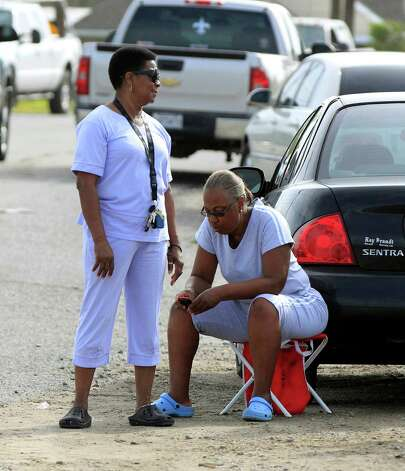 Joyce Woods, left, and Alice Turner, wait in the hopes of returning to their homes in Braithwaite, La., after Isaac flooded the community, Friday, Aug. 31, 2012.  Isaac crawled into the central U.S. on Friday, leaving behind a soggy mess in Louisiana.  It will be a few days before the water recedes and people in flooded areas can return home. New Orleans itself was spared, thanks in large part to a levee system fortified after Katrina devastated the Gulf Coast in 2005. (AP Photo/Gerald Herbert) Photo: Gerald Herbert, Associated Press / AP