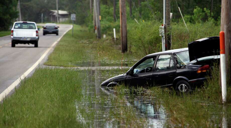 Returning residents drive past a swamped vehicle in Hancock County, Miss., Friday, Aug. 31, 2012.  Some neighborhoods flooded as Isaac continued dumping heavy rains on its slow trek northward. Some coastal businesses and roads reopened, but many people who had evacuated still couldn't make it home because of standing water in low-lying areas and along rivers.  (AP Photo/Rogelio V. Solis) Photo: Rogelio V. Solis, Associated Press / AP