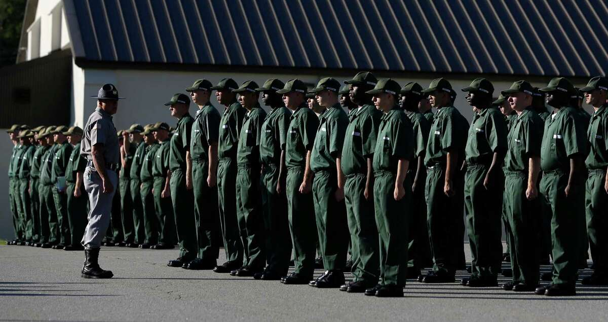 Inmates stand during morning flag formation at the Moriah Shock Incarceration Correctional Facility Wednesday, Aug. 22, 2012, in Mineville, N.Y. New York corrections officials say they have graduated more than 40,000 inmates from military-style boot camps over the past 25 years and most never come back. Established as an alternative to regular prison in the 1980s in efforts across the country, which got mixed reviews and dropped by several states, New York officials have kept three shock camps going with a model they consider effective, with lower recidivism and saving money.