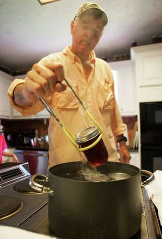 Tim Dyring removes jars of homemade beautyberry jelly from a pot of boiling water. Photo: J. Patric Schneider, Photographer / © 2012 Houston Chronicle