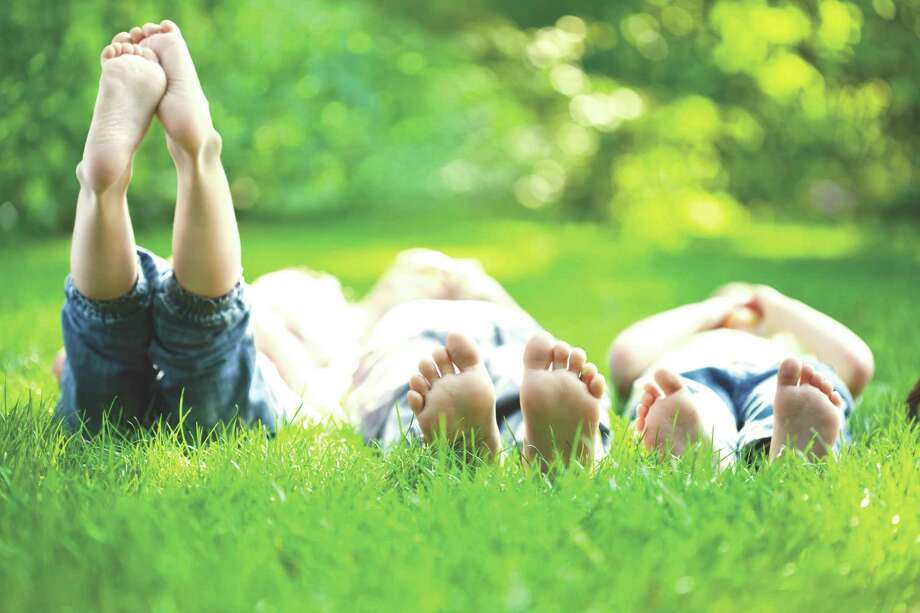 Group of happy children lying on green grass outdoors in spring park / Igor Yaruta - Fotolia