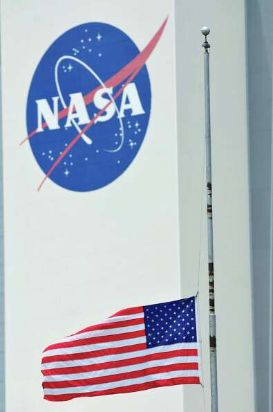 The U.S. flag flies at half mast outside the Vehicle Assembly Building in honor of Neil Armstrong at