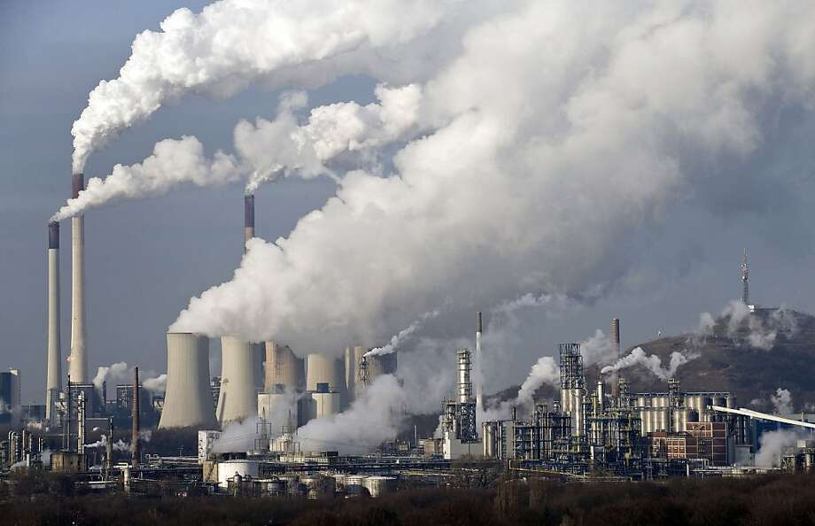 A coal power station in Gelsenkirchen, Germany, spews steam and smoke. Europe's cap-and-trade system, which is meant to reduce such emissions, has been subject to economic winds: In 2011, the price of carbon emission permits fell by half during a six-month period because investors cut their activity in the market. Right, a solar energy system is installed in a home in Palm Springs. California leads the United States in solar power generation. Photo: Martin Meissner, Associated Press